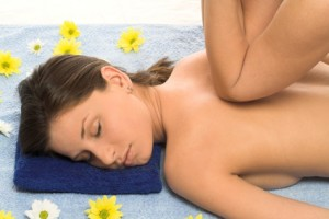 Brunette getting a back massage in the spa salon with flowers spread around